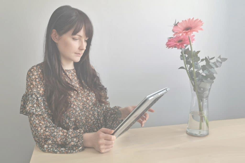 Tummahiuksinen nainen istuu pöydän ääressä ja katsoo kädessään olevaa tablettiaan. Edessä punainen orkidea ja taustalla harmaa seinä.