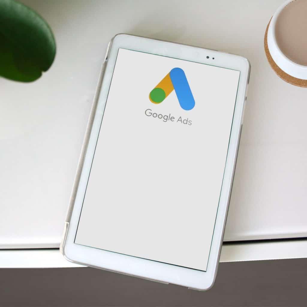"""Valkoinen tabletti valkoisella tasolla, oikeassa yläkulmassa kahvikuppi ja vasemmalla näkyy vähän vihreää kasvia. Tabletissa keltasinivihreä kuvio ja teksti """"Google Ads"""""""