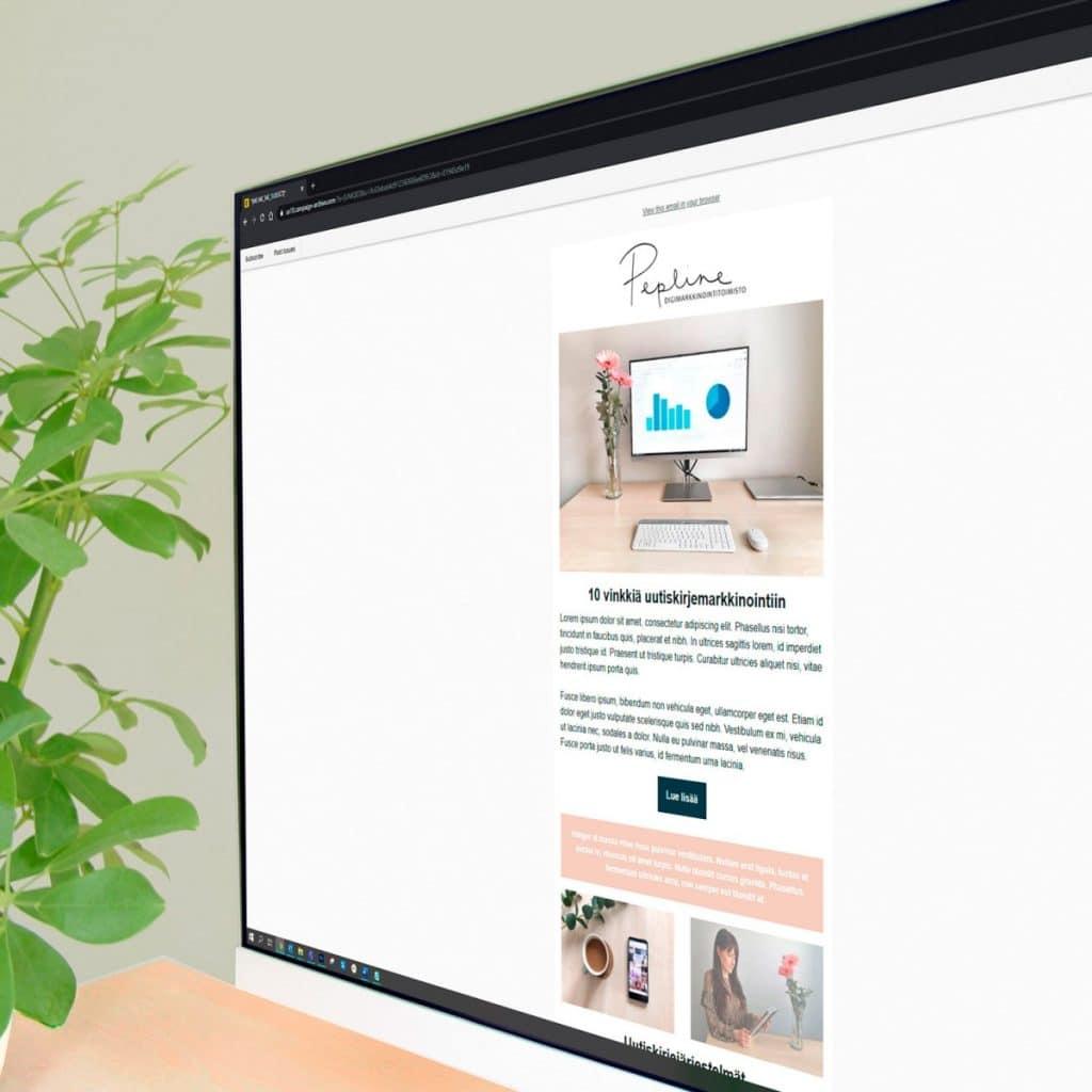 Tietokoneen näyttö, jossa Peplinen sähköpostimarkkinointia. Taustalla vihreä kasvi sekä vaaleanharmaa seinä.