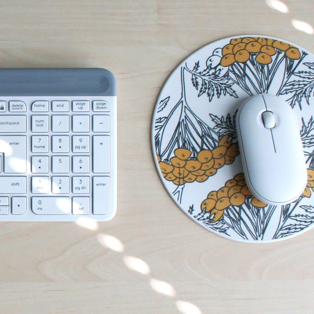 Koivunvärisellä pöydällä näppäimistö sekä hiiri ja valkomustakeltainen hiirimatto.