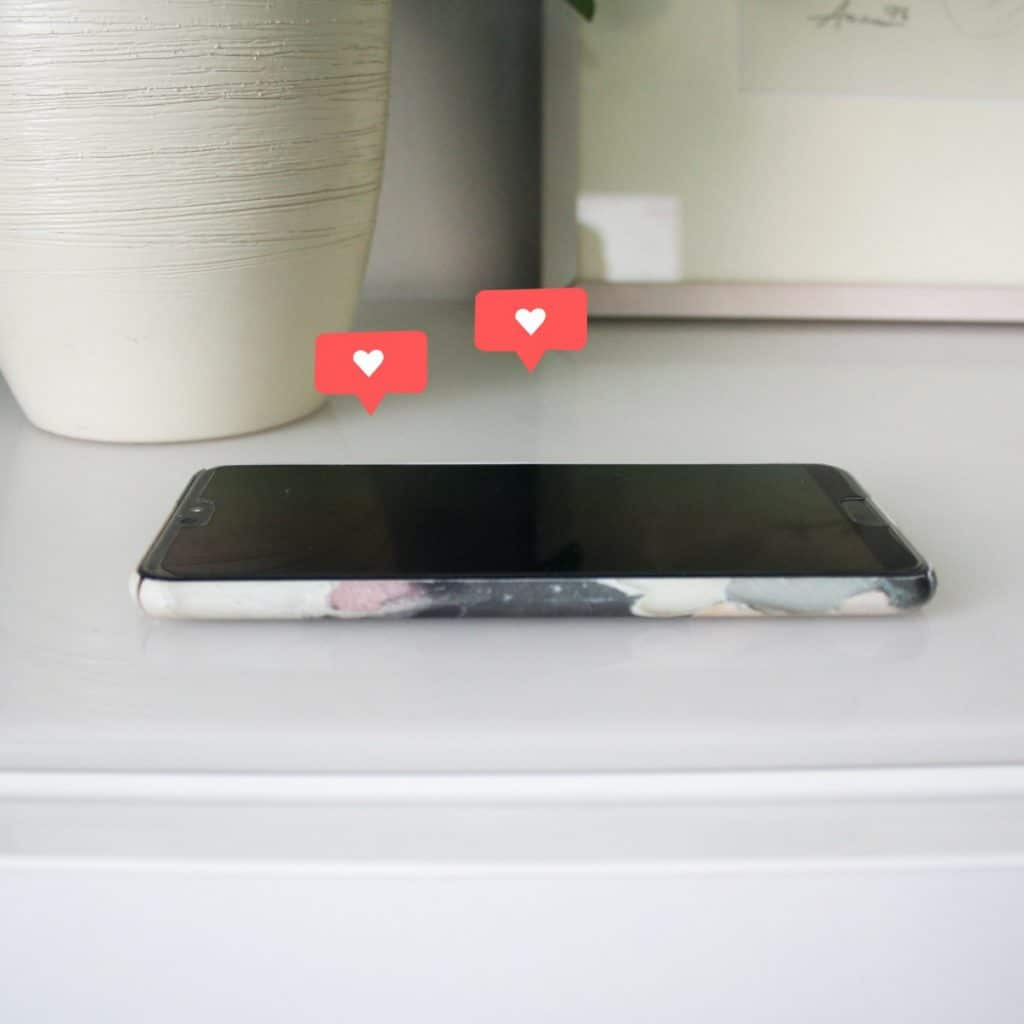 Valkoisella tasolla puhelin, jonka yläpuolella kaksi sosiaalisen median Instagramin sydäntykkäyskuvaketta. Taustalla kukkaruukku sekä taulu.