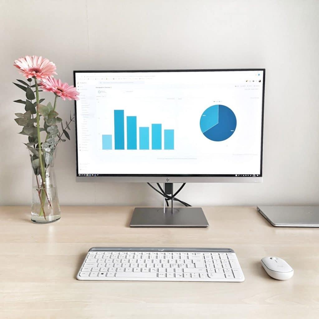 Tietokone, näppäimistö, hiiri, näyttö ja kukkia koivunvärisellä työpöydällä. Näytössä sinisiä kaavioita ja kuvan taustalla vaalea seinä.
